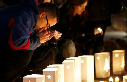 A man reacts placing candles on a makeshift memorial in honor of the victims who died a day earlier when a gunman opened fire in an elementary school, Saturday, Dec. 15, 2012, in Newtown, Conn. The man, who died from a self-inflicted wound, allegedly killed his mother at their home and then opened fire Friday inside the Sandy Hook Elementary school, massacring 26 people, including 20 children. &#40;AP Photo&#47;Julio Cortez&#41; <span class=meta>(AP Photo&#47; Julio Cortez)</span>