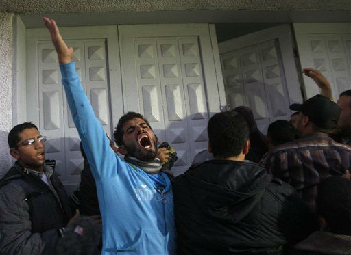 Palestinian men react at hospital after the body of Ahmed Jabari, head of the Hamas military wing, was brought,  in Gaza City, Wednesday, Nov. 14, 2012. The Israeli military said its assassination of the Hamas military commander marks the beginning of an operation against Gaza militants. &#40;AP Photo&#47;Hatem Moussa&#41; <span class=meta>(AP Photo&#47; Hatem Moussa)</span>