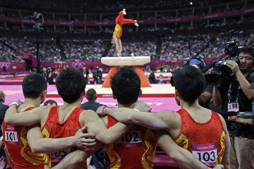 Chinese gymnasts stand together and watch a fellow gymnast on the pommel horse during the Artistic Gymnastic men&#39;s team final at the 2012 Summer Olympics, Monday, July 30, 2012, in London. &#40;AP Photo&#47;Julie Jacobson&#41; <span class=meta>(AP Photo&#47; Julie Jacobson)</span>