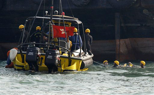 Frogmen from firefighting team retrieve a body, right, Tuesday Oct. 2, 2012 near a boat, unseen, after it collided and sank Monday night near Lamma Island, off the southwestern coast of Hong Kong Island. The boat packed with revelers on a long holiday weekend collided with a ferry and sank off Hong Kong, killing at least 36 people and injuring dozens, authorities said.  &#40;AP Photo&#47;Vincent Yu&#41; <span class=meta>(AP Photo&#47; Vincent Yu)</span>