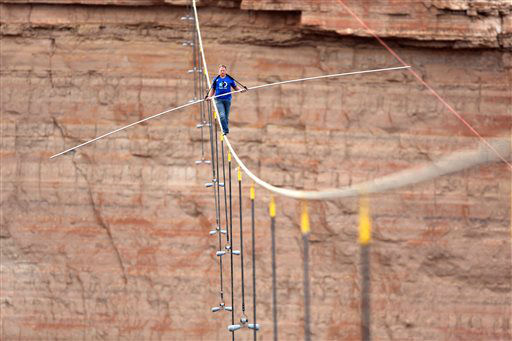 In this photo provided by the Discovery Channel, aerialist Nik Wallenda walks a 2-inch-thick steel cable taking him a quarter mile over the Little Colorado River Gorge, Ariz. on Sunday, June 23, 2013. The daredevil successfully traversed the tightrope strung 1,500 feet above the chasm near the Grand Canyon in just more than 22 minutes, pausing and crouching twice as winds whipped around him and the cable swayed. &#40;AP Photos&#47;Discovery Channel, Tiffany Brown&#41; <span class=meta>(AP Photo&#47; Tiffany Brown)</span>