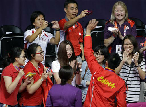 Chinese fans get a close look of China&#39;s Lin Dan after the medal ceremony of the men&#39;s singles badminton at the 2012 Summer Olympics, Sunday, Aug. 5, 2012, in London. Lin won 15-21, 21-10, 21-19 to repeat his victory over Malaysia&#39;s Lee Chong Wei in the Beijing Games final, and claim his sixth Olympic or world title. &#40;AP Photo&#47;Andres Leighton&#41; <span class=meta>(AP Photo&#47; Andres Leighton)</span>