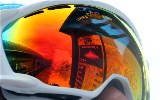 The forecast for tomorrow's temperature is reflected in the ski goggles of a volunteer at the Sochi 2014 Winter Olympics, Tuesday, Feb. 11, 2014, in Krasnaya Polyana, Russia. Warm temperatures in the mountains made the snow too soft and caused the cancellation of Women's downhill training on Tuesday. (AP Photo/Luca Bruno)