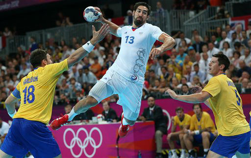 France&#39;s Nikola Karabatic, center, leaps in the air to score past Sweden&#39;s Tobias Karlsson, left, and Sweden&#39;s Kim Andersson, right, during the men&#39;s handball gold medal match at the 2012 Summer Olympics, Sunday, Aug. 12, 2012, in London. &#40;AP Photo&#47;Petr David Josek&#41; <span class=meta>(AP Photo&#47; Petr David Josek)</span>