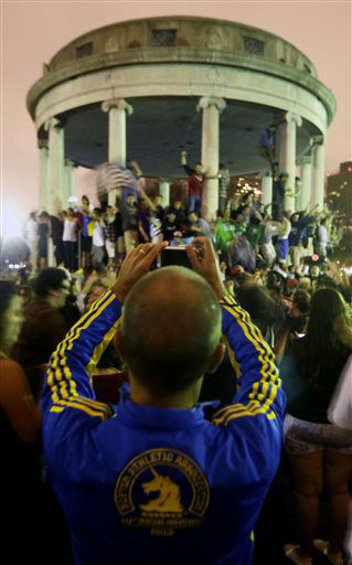Andre Savazoni, 38, of Brazil, who participated in his second Boston Marathon this week, takes a photo of a crowd gathered at Boston Common after the final suspect in the Boston Marathon bombing was arrested, Friday, April 19, 2013, in Boston. Marathon bombing suspect Dzhokhar Tsarnaev was captured in Watertown, Mass. The 19-year-old college student wanted in the bombings was taken into custody Friday evening after a manhunt that left the city virtually paralyzed and his older brother and accomplice dead.  &#40;AP Photo&#47;Julio Cortez&#41; <span class=meta>(AP Photo&#47; Julio Cortez)</span>