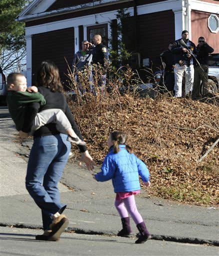 A mother runs with her children as police above canvass homes in the area following a shooting at the Sandy Hook Elementary School in Newtown, Conn., about 60 miles &#40;96 kilometers&#41; northeast of New York City, Friday, Dec. 14, 2012. An official with knowledge of Friday&#39;s shooting said 27 people were dead, including 18 children. &#40;AP Photo&#47;Jessica Hill&#41; <span class=meta>(AP Photo&#47; Jessica Hill)</span>