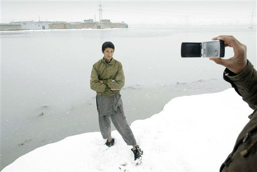 An Afghan boy poses for his friend&#39;s camera during a snowstorm in Kabul, Afghanistan, Monday, Feb. 4, 2013. Kabul has been experiencing below freezing weather and snow for several days. &#40;AP Photo&#47;Musadeq Sadeq&#41; <span class=meta>(AP Photo&#47; Musadeq Sadeq)</span>