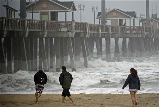 Beachgoers walk in the wind and rain as waves generated by Hurricane Sandy crash into Jeanette&#39;s Pier in Nags Head, N.C., Saturday, Oct. 27, 2012 as the storm churns up the east coast. Hurricane Sandy, upgraded again Saturday just hours after forecasters said it had weakened to a tropical storm, was barreling north from the Caribbean and was expected to make landfall early Tuesday near the Delaware coast, then hit two winter weather systems as it moves inland, creating a hybrid monster storm. &#40;AP Photo&#47;Gerry Broome&#41; <span class=meta>(AP Photo&#47; Gerry Broome)</span>
