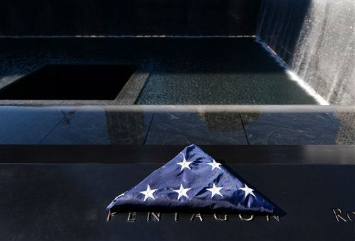 A folded American flag sits by the section of engraved names on the border of one of the reflecting pools of the World Trade Center Memorial, of those who died at the Pentagon, during the 11th anniversary observance, in New York, Tuesday Sept. 11, 2012. &#40;AP Photo&#47;Justin Lane, Pool&#41; <span class=meta>(AP Photo&#47; Justin Lane)</span>