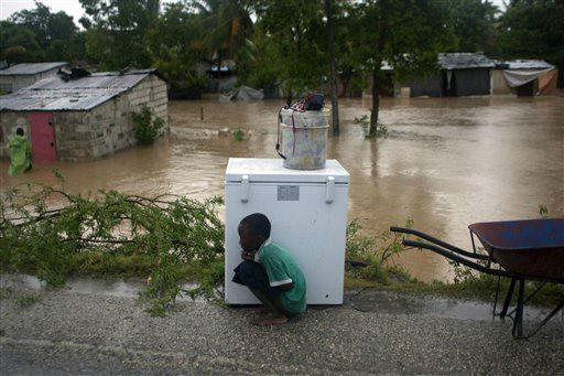 A boy tries to take cover from the cold behind an appliance sitting higher than the floodwaters triggered by Tropical Storm Isaac in Port-au-Prince, Haiti, Saturday Aug. 25, 2012. Tropical Storm Isaac swept across Haiti&#39;s southern peninsula early Saturday, dousing a capital city prone to flooding and adding to the misery of a poor nation still trying to recover from the 2010 earthquake. &#40;AP Photo&#47;Dieu Nalio Chery&#41; <span class=meta>(AP Photo&#47; Dieu Nalio Chery)</span>