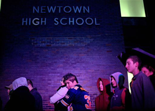 Josue Gonzales, right, embraces Lindsay Zawesza, as they wait in line to enter Newtown High School for a memorial vigil attended by President Barack Obama for the victims of the Sandy Hook Elementary School shooting, Sunday, Dec. 16, 2012, in Newtown, Conn. A gunman walked into Sandy Hook Elementary School in Newtown Friday and opened fire, killing 26 people, including 20 children. &#40;AP Photo&#47;David Goldman&#41; <span class=meta>(AP Photo&#47; David Goldman)</span>