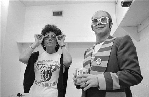 Elizabeth Taylor adjusts her glasses during a backstage visit on Wednesday, July 7, 1976 at Philadelphia?s Spectrum Theater with be speckled British rock star Elton John. Miss Taylor went to the theater to watch John perform on the last day of his concert in the city. Both are wearing ?I?m nearly famous? Buttons, the title of a record album by British pop star Cliff Richard. This picture was taken by British photographer David Nutter and became available on Thursday, July 8. &#40;AP Photo&#47;David Nutter&#41; <span class=meta>(AP Photo&#47; David Nutter)</span>