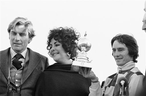 Actress Elizabeth Taylor and her escort, former Navy Secretary John Warner, left, present a trophy to jockey Sandy Hawley who rode Youth to victory in the Washington D.C. International race on Saturday, Nov. 6, 1976 in Laurel, Maryland. &#40;AP Photo&#41; <span class=meta>(AP Photo&#47; Anonymous)</span>