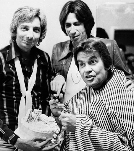 Television&#39;s Dick Clark helps cut his 47th birthday cake during a break in rehearsals for an upcoming television special in Santa Monica, Ca., December 1, 1976. Helping him celebrate are &#40;l&#41; singer Barry Manilow and comedian David Brenner. Clark is wearing a smock to protect him while he is madeup. &#40;AP Photo&#41; <span class=meta>(AP Photo&#47; Anonymous)</span>