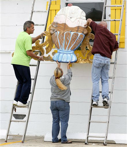 Richard Caguilat, left, William Disburger, right, and Carol Seymour remove a large sign from the Sea Shell Ice Cream shop in Wildwood, N.J., Saturday, Oct. 27, 2012, in preparation for Hurricane Sandy. From the lowest lying areas of the Jersey shore, where residents were already being encouraged to leave, to the state&#39;s northern highlands, where sandbags were being filled and cars moved into parking lots on high ground, New Jersey began preparing in earnest for Hurricane Sandy. &#40;AP Photo&#47;Mel Evans&#41; <span class=meta>(AP Photo&#47; Mel Evans)</span>