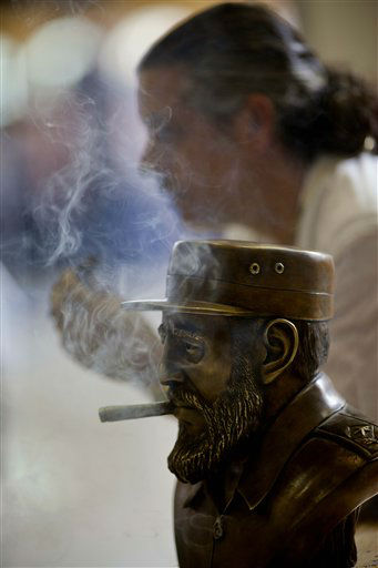 A bronze statue depicting Cuba's leader Fidel Castro smoking, made by the Cuban artist Ernesto Milanes, background, is seen during the inauguration of the 15th Cigar Festival in Havana, Cuba, Tuesday, Feb. 26, 2013. Cigar enthusiasts from around the world come to Cuba during the annual celebration to visit tobacco farms and factories and savor new cigar brands. (AP Photo/Ramon Espinosa)