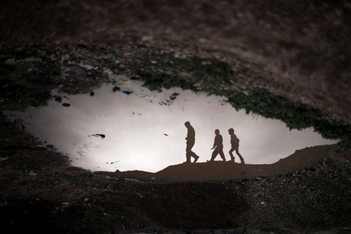 Displaced Syrian children are reflected in a puddle as they walk through an olive tree field near the Azaz camp for displaced people, north of Aleppo province, Syria, Thursday, Feb. 21, 2013. According to Syrian activists the number of people in the Azaz camp has grown by 3,000 in the last weeks due to heavier shelling by government forces. &#40;AP Photo&#47;Manu Brabo&#41; <span class=meta>(AP Photo&#47; Manu Brabo)</span>
