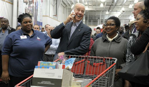 Vice President Joe Biden smiles as he makes a call on the cell phone of Costco employee Ivey Stewart, left, after shopping at the a Costco store in Washington, Thursday, Nov. 29, 2012. Biden went shopping for presents and to highlight the importance of renewing middle-class tax cuts so families and businesses have more certainty at this critical time for our economy. &#40;AP Photo&#47;Susan Walsh&#41; <span class=meta>(AP Photo&#47; Susan Walsh)</span>