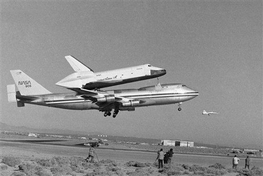 America?s Space Shuttle Enterprise, rides atop a giant 747 on its first test flight at Edwards Air Force Base, Calif., Feb. 18, 1977. In the right foreground is a chase plane. Cameramen are shown on the ground. &#40;AP Photo&#41; <span class=meta>(AP Photo&#47; Anonymous)</span>