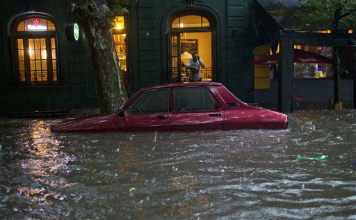 A car is submerged in flood water in front of a home in Buenos Aires, Argentina, Thursday, Dec. 6, 2012.  Heavy rain flooded the capital on Thursday. &#40;AP Photo&#47;Natacha Pisarenko&#41; <span class=meta>(AP Photo&#47; Natacha Pisarenko)</span>