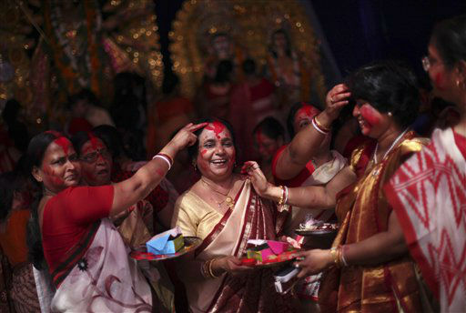 Indian Hindu women apply vermillion powder on each other during Durga Puja festivities in New Delhi, India, Wednesday, Oct. 24, 2012. The festival commemorates the slaying of a demon king by lion-riding, ten armed goddess Durga, marking the triumph of good over evil. &#40;AP Photo&#47;Altaf Qadri&#41; <span class=meta>(AP Photo&#47; Altaf Qadri)</span>