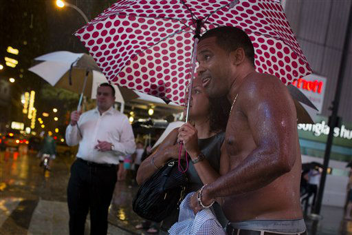 "<div class=""meta image-caption""><div class=""origin-logo origin-image ""><span></span></div><span class=""caption-text"">Soaked pedestrians huddle under an umbrella heavy rains pass over Times Square, Thursday, July 26, 2012, in New York. The storm resulted in more than 20,000 customers without power in the Elmira area in upstate New York, where buildings were damaged, power lines and trees toppled, and hospitals placed on disaster status after a possible tornado hit the city Thursday afternoon. (AP Photo/John Minchillo) (AP Photo/ John Minchillo)</span></div>"