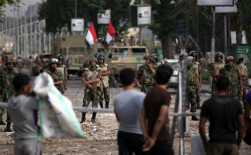 "<div class=""meta ""><span class=""caption-text "">Supporters of ousted President Mohammed Morsi protest as army soldiers guard at the Republican Guard building in Nasr City, Cairo, Egypt, Tuesday, July 9, 2013. Egyptian security forces killed dozens of supporters of Egypt's ousted president in one of the deadliest single episodes of violence in more than two and a half years of turmoil. The toppled leader's Muslim Brotherhood called for an uprising, accusing troops of gunning down protesters, while the military blamed armed Islamists for provoking its forces. (AP Photo/Khalil Hamra) (AP Photo/ Khalil Hamra)</span></div>"