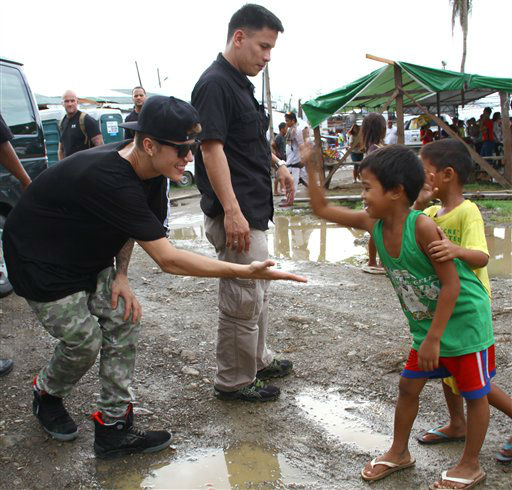"<div class=""meta ""><span class=""caption-text "">Justin Bieber, left, exchanges high-fives with children survivors of typhoon Haiyan during his visit Tuesday, Dec. 10, 2013 to Tacloban city, Leyte province in central Philippines. The teen heartthrob Bieber arrived Tuesday in the Philippines, where he has launched a campaign to help victims of last month's killer typhoon. (AP Photo)</span></div>"
