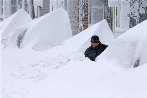 John Silver shovels between buried cars in front of his home on Third street in South Boston, Saturday, Feb. 9, 2013. (AP Photo/Gene J. Puskar)