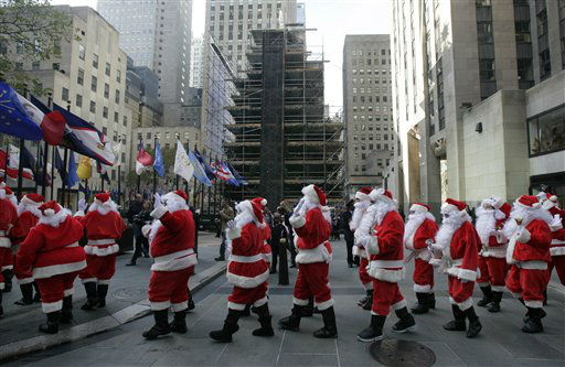 Volunteers of America Santas walk past the Rockefeller Center Christmas tree during their 110th annual Sidewalk Santa Parade, in New York,  Friday, Nov. 23, 2012. The donations they raise are used for a holiday food voucher program for needy residents. &#40;AP Photo&#47;Richard Drew&#41; <span class=meta>(AP Photo&#47; Richard Drew)</span>