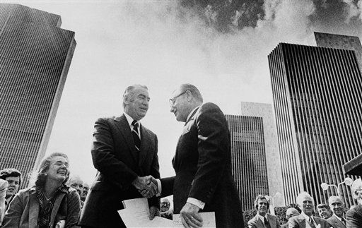 While Happy Rockefeller, left, smiles, New York Gov. Hugh Carey shakes the hand of former New York Gov. Nelson A. Rockefeller after ceremonies on Friday, Oct. 6, 1978 in Albany, which renamed the ten-building complex the Governor Nelson A. Rockefeller Empire State Plaza.     At the right is Republican gubernatorial candidate Perry Duryea, clapping.    The tower, the highest building in upstate New York is at the left, while two of the four Agency Buildings are at the right. &#40;AP Photo&#41; <span class=meta>(AP Photo&#47; Hoy)</span>