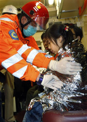 A young survivor is comforted by a rescuer after a collision involving two vessels in Hong Kong Tuesday, Oct. 2, 2012. Authorities in Hong Kong have rescued 101 people after a ferry collided with a boat and sank. A local broadcaster says eight people died. The government said in a statement that the ferry was carrying about 120 people when the accident happened Monday night near Lamma Island, off the southwestern coast of Hong Kong Island. Few other details were given. &#40;AP Photo&#47;Vincent Yu&#41; <span class=meta>(AP Photo&#47; Vincent Yu)</span>