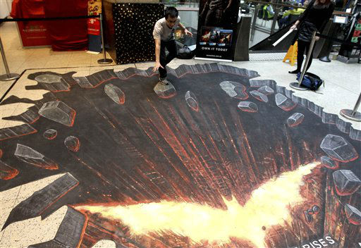 A young man pretends to balance on a piece of falling rock in a 3D chalk art drawing of a scene from &#34;The Dark Knight Rises&#34; film at a CBD shopping mall in Sydney, Australia, Wednesday, Nov. 28, 2012. &#40;AP Photo&#47;Rob Griffith&#41; <span class=meta>(AP Photo&#47; Rob Griffith)</span>
