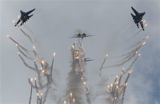 Su-27 jets of aerobatics team Russkiye Vityasy, or Russian Knights, release decoys as they perform aerial demonstrations during the International Maritime Defense show in St.Petersburg, Russia, Sunday, July 7, 2013. &#40;AP Photo&#47;Dmitry Lovetsky&#41; <span class=meta>(AP Photo&#47; Dmitry Lovetsky)</span>