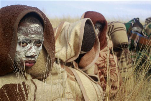 A Xhosa boy covered with a blanket and smeared with chalky mud sits in a field as he and others undergo a traditional Xhosa male circumcision ceremony into manhood near the home of former South African president Nelson Mandela in Qunu, South Africa, Sunday, June 30, 2013. &#40;AP Photo&#47;Schalk van Zuydam&#41; <span class=meta>(AP Photo&#47; Schalk van Zuydam)</span>