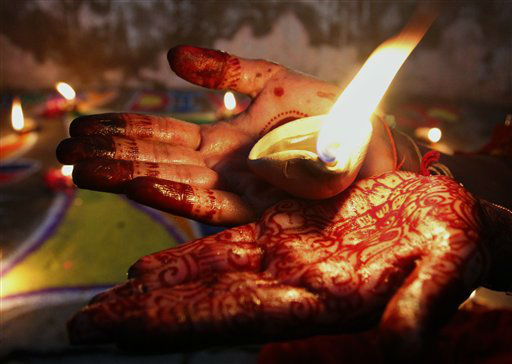 A Pakistani Hindu girl holds an earthen lamp while decorating an area of her house to celebrate Diwali, the Hindu festival of lights, Tuesday, Nov. 13, 2012 in Karachi, Pakistan. Hindus across the country are celebrating Diwali, where people decorate their homes with light and set off firecrackers. &#40;AP Photo&#47;Shakil Adil&#41; <span class=meta>(AP Photo&#47; Shakil Adil)</span>