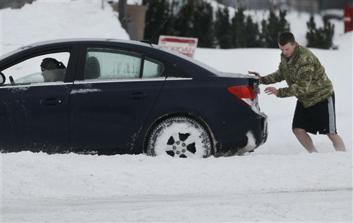An unidentified man pushes a car through a snow covered intersection in Lawrence, Kan., Thursday, Feb. 21, 2013.  Kansas was the epicenter of a winter storm, with parts of the state buried under 14 inches of powdery snow, but winter storm warnings stretched from eastern Colorado through Illinois.  &#40;AP Photo&#47;Orlin Wagner&#41; <span class=meta>(AP Photo&#47; Orlin Wagner)</span>