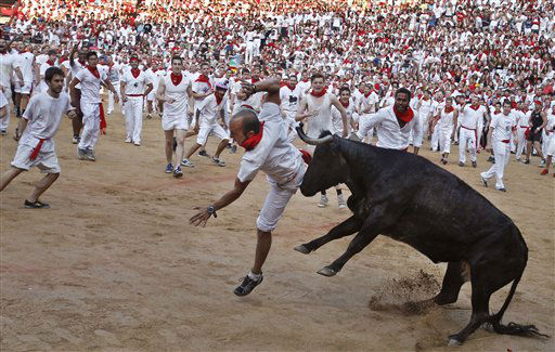 A reveler is pushed by a Torrestrella ranch bull at the bull ring at the end of the fifth running of the bulls, at the San Fermin fiestas, in Pamplona northern Spain on Thursday, July 11, 2013. &#40;AP Photo&#47;Alvaro Barrientos&#41; <span class=meta>(AP Photo&#47; Alvaro Barrientos)</span>