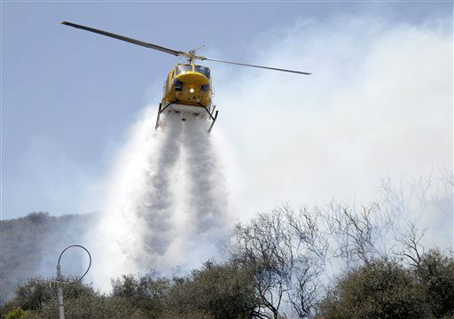 A helicopter drops water on a hotspot over a hill near Thousand Oaks, Calif. on Thursday, May 2, 2013. A wildfire fanned by gusty Santa Ana winds raged along the fringes of Southern California communities on Thursday, forcing evacuation of homes and a university while setting recreational vehicles ablaze. &#40;AP Photo&#47;Nick Ut&#41; <span class=meta>(AP Photo&#47; Nick Ut)</span>
