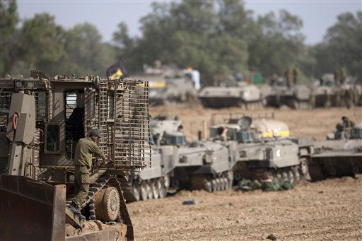 Israeli soldiers work on their a tanks in a staging ground near the border with Gaza Strip, southern Israel, Friday, Nov. 16, 2012. Fierce clashes between Israeli forces and Gaza militants are continuing for the third day.&#40;AP Photo&#47;Ariel Schalit&#41; <span class=meta>(AP Photo&#47; Ariel Schalit)</span>