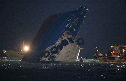 Rescuers check on a half submerged boat after it collided Monday night near Lamma Island, off the southwestern coast of Hong Kong Island Tuesday, Oct. 2, 2012. Authorities in Hong Kong have rescued 101 people after a ferry collided with a tugboat and sank. A local broadcaster says eight people died. &#40;AP Photo&#47;Kin Cheung&#41; <span class=meta>(AP Photo&#47; Kin Cheung)</span>