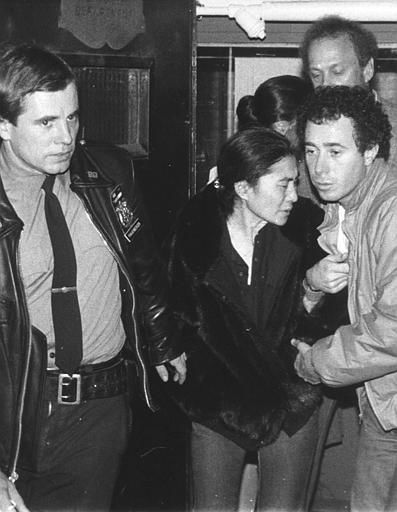 Yoko Ono, center, is aided by a policeman and David Geffen, right, of Geffen Records as she leaves Roosevelt Hospital in New York late Monday night, Dec. 8, 1980 after the death of her husband John Lennon.  Lennon was shot outside his apartment in New York after returning from the recording studio. &#40;AP Photo&#47;Lyndon Fox&#41; <span class=meta>(AP Photo&#47; LYNDON FOX)</span>