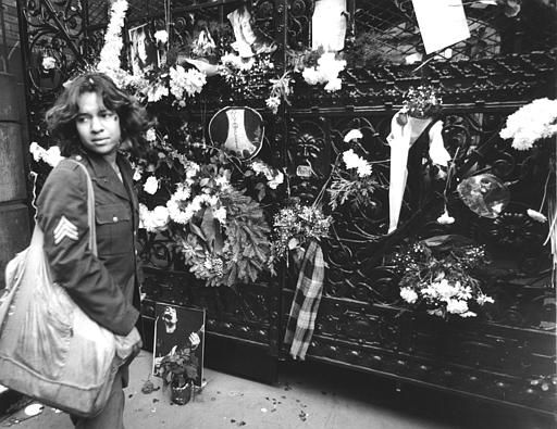 A young woman stands near the gate of the Dakota apartment building Tuesday, Dec. 9, 1980 in New York. Flowers have been placed on the gate, the site of Monday night`s fatal shooting of former Beatle John Lennon. Hundreds of fans came to the site to pay their respects. &#40;AP Photo&#41; <span class=meta>(AP Photo&#47; XAG XCO)</span>
