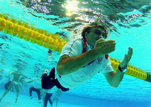 Croatia coach Ratko Rudic swims after jumping in the pool to celebrate his team&#39;s 8-6 victory over Italy during the men&#39;s water polo gold medal match at the 2012 Summer Olympics, Sunday, Aug. 12, 2012, in London. &#40;AP Photo&#47;Julio Cortez&#41; <span class=meta>(AP Photo&#47; Julio Cortez)</span>
