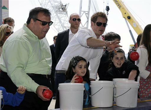 Britain&#39;s Prince Harry, center, and New Jersey Gov. Chris Christie, left, toss balls for Taylor Cirigliano, 11, right, and sister Allie Cirigliano, 7, at a Ball Toss game on the boardwalk, while visiting the area hit by Superstorm Sandy, Tuesday, May 14, 2013, in Seaside Heights, N.J.  Prince Harry began a tour  of New Jersey?s storm-damaged coastline, inspecting dune construction, walking past destroyed homes and shaking hands with police and other emergency workers.  New Jersey sustained about &#36;37 billion worth of damage from the storm. &#40;AP Photo&#47;Mel Evans&#41; <span class=meta>(AP Photo&#47; Mel Evans)</span>