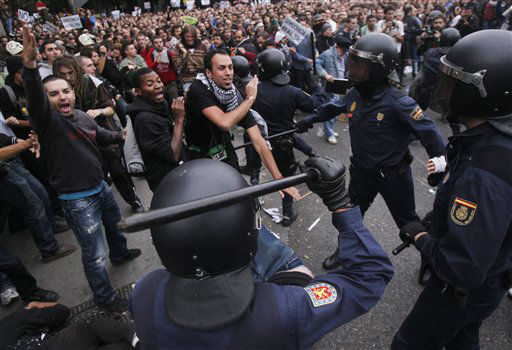 Protestors clash with the police riots during the march to the parliament against austerity measures announced by the Spanish government in Madrid, Spain, Tuesday, Sept. 25, 2012. Spain&#39;s Parliament has taken on the appearance of a heavily guarded fortress with dozens of police blocking access from every possible angle, hours ahead of a protest against the conservative government&#39;s handling of the economic crisis. The demonstration, organized behind the slogan &#39;Occupy Congress,&#39; is expected to draw thousands of people. It is due to start around 1730 GMT Tuesday. Madrid authorities said some 1,300 police would be deployed. The protestors call for Parliament to be dissolved and fresh elections held, claiming the government&#39;s austerity measures show the ruling Popular Party misled voters to get elected last November. &#40;AP Photo&#47;Andres Kudacki&#41; <span class=meta>(AP Photo&#47; Andres Kudacki)</span>