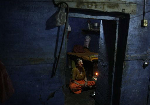 An elderly Indian widow performs morning rituals at the non-governmental organization Sulabh International in Varanasi, India, Monday, May 27, 2013. In India, being a widow remains one of the worst stigmas. When her husband dies, the widow often becomes a pariah, excluded from family gatherings for fear the mere fall of her shadow will bring bad luck and tragedy. In the North, many journey to the holy cities of Vrindavan and Varanasi, where they beg, and are paid a pittance to recite prayers in the temple as they wait for the end. The NGO Sulabh International takes care of the welfare, protection, maintenance and education of widows so that their living conditions improve. &#40;AP Photo&#47;Rajesh Kumar Singh&#41; <span class=meta>(AP Photo&#47; Rajesh Kumar Singh)</span>
