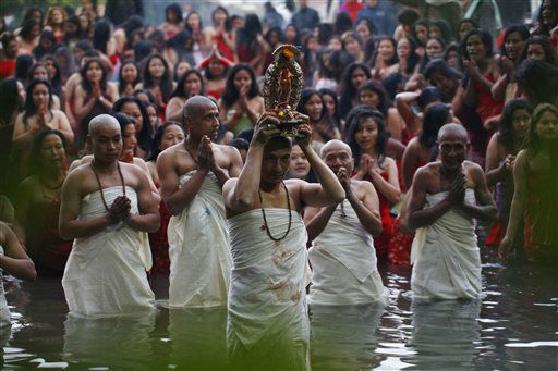 A Nepalese Hindu priest, center, carries the idol of a deity as devotees gets ready to take holy dips at the Salinadi River on the first day of Madhav Narayan festival, in Sankhu, northeast of Katmandu, Nepal, Sunday, Jan. 27, 2013. Unmarried Hindu women pray to get a good husband while the married women pray for the longevity of their husbands by observing day long fast during the month long festival. &#40;AP Photo&#47;Niranjan Shrestha&#41; <span class=meta>(AP Photo&#47; Niranjan Shrestha)</span>
