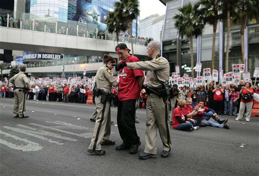 Las Vegas Metropolitan Police officers lead away a protestor during a civil disobedience demonstration by Culinary Union workers outside the Cosmopolitan Hotel-Casino, Wednesday, March 20, 2013, in Las Vegas. Nearly 98 protestors were arrested during the demonstration in which they sat on and blocked traffic along Las Vegas Boulevard. Workers have been in contract talks with Cosmopolitan Las Vegas owner Deutsche  Bank for two years. &#40;AP Photo&#47;Julie Jacobson&#41; <span class=meta>(AP Photo&#47; Julie Jacobson)</span>