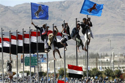 Supporters of Yemen's former President Ali Abdullah Saleh climb on flag poles during a rally marking the anniversary of his power handover in Sanaa, Yemen, Wednesday, Feb. 27, 2013. (AP Photo/Hani Mohammed)